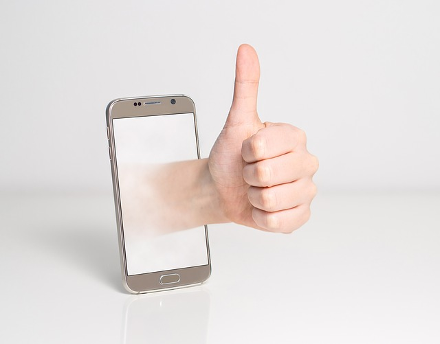 Thumbs up coming out of a mobile phone